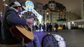 Il musicista della via nel centro di Mosca canta e gioca la chitarra ed i tamburi video d archivio
