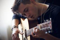Il musicista esegue da solo sulla chitarra acustica della sei-corda fotografia stock