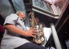 Il musicista gioca il sassofono per le donazioni sulla via del silom Fotografia Stock Libera da Diritti