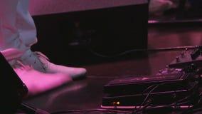 Il musicista sulla fase batte i piedi il suo piede a tempo con la musica stock footage