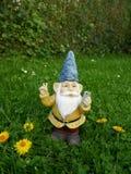 Il nano divertente del giardino con il telefono cellulare su un prato verde fa il segno di pace Fotografia Stock Libera da Diritti