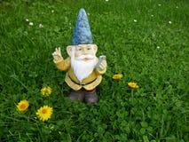 Il nano divertente del giardino con il telefono cellulare su un prato verde fa il segno di pace Immagini Stock