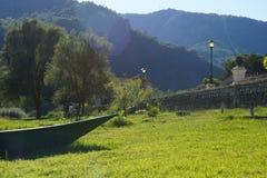 Il naso della barca sulla banca del fiume sull'erba, accanto all'argine con le lanterne, sulle alte montagne di orizzonte, o Immagini Stock