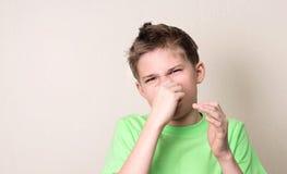 Il naso di pizzichi del bambino del ritratto del primo piano con le mani delle dita guarda con immagini stock libere da diritti