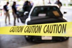 Il nastro di cautela protegge il veicolo in traini di ricerca della scena del crimine fotografia stock