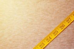 Il nastro di misurazione di colore giallo con gli indicatori numerici sotto forma di centimetri o di pollici si trova su un tessu Fotografie Stock Libere da Diritti