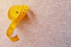 Il nastro di misurazione giallo con gli indicatori numerici sotto forma di centimetri o di pollici si trova su un tessuto tricott Fotografie Stock