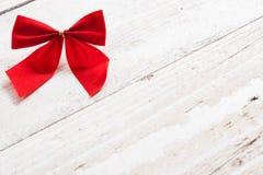Il nastro e l'arco rossi decorativi su un fondo di bianco hanno dipinto la r Fotografia Stock Libera da Diritti