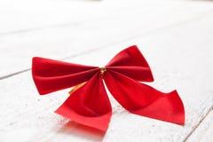 Il nastro e l'arco rossi decorativi su un fondo di bianco hanno dipinto la r Fotografie Stock Libere da Diritti