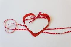 Il nastro sottile rosso e bianco ha completato con due cuori di carta del biglietto di S. Valentino Fotografia Stock Libera da Diritti