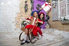 Il Natale è già qui Ragazza che sledding con il contenitore di regalo di natale Le piccole ragazze sveglie hanno ricevuto i regal immagine stock