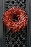 Il Natale all'aperto si avvolge fatto dei peperoncini roventi secchi che appendono alla porta di entrata Fotografia Stock Libera da Diritti
