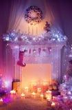 Il Natale camino, posto del fuoco del calzino della corona, ha decorato l'interno Immagine Stock