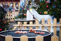 Il Natale commercializza in quadrato rosso, Mosca Preparazione delle salsiccie e delle salsiccie su una griglia per i hot dog Fotografia Stock Libera da Diritti