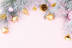 Il Natale confina con i rami dell'abete, i coni della conifera, le palle di natale e gli ornamenti sul fondo di rosa pastello Fotografia Stock Libera da Diritti