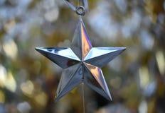 Il Natale d'argento della stella sopra il bokeh del cuore ha offuscato il fondo fotografia stock libera da diritti