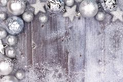 Il Natale d'argento orna il confine d'angolo superiore con neve su legno Fotografie Stock