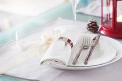 Il Natale decorato elegante presenta la regolazione con le decorazioni moderne della coltelleria, del tovagliolo, dell'arco e di  Immagine Stock