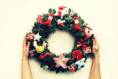 Il Natale decorato si avvolge nelle mani di una donna Su fondo bianco Fotografia Stock Libera da Diritti