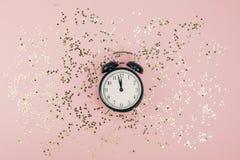 Il Natale del nuovo anno la vista di cima che pone pianamente la sveglia nera dodici ha coperto la carta rosa millenaria di color fotografia stock