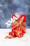 Il natale di parola che appende durante i regali di Natale rossi Immagine Stock