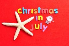 Il natale di parole a luglio nelle lettere variopinte con una stella marina e una figurina di Santa Fotografia Stock