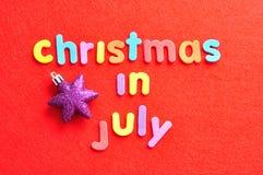 Il natale di parole a luglio nelle lettere variopinte su un fondo rosso Immagini Stock