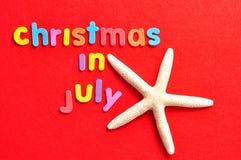 Il natale di parole a luglio su un fondo rosso con una stella marina Fotografie Stock
