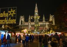 Il Natale di visita della gente commercializza vicino al municipio alla sera Fotografie Stock Libere da Diritti