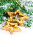 Il Natale dorato stars con il ramo e la neve del pino Fotografia Stock Libera da Diritti