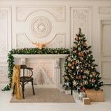 Il Natale ed il nuovo anno hanno decorato la stanza interna con i presente e l'albero del nuovo anno immagini stock libere da diritti