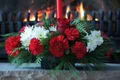 Il Natale elegante fiorisce l'esposizione con la combustione del camino nei precedenti fotografia stock
