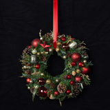 Il Natale fatto a mano fresco si avvolge decorato con rosso e decorazioni di Natale dell'oro, abete-coni e noci Fotografia Stock