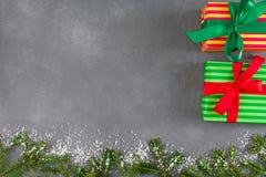 Il natale ha colorato i contenitori di regalo, spazio della copia sul fondo grigio della tavola Fotografie Stock