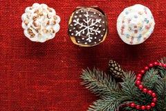 Il Natale ha decorato i bigné alla vista superiore del fondo rosso della tela da imballaggio Fotografie Stock