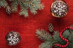 Il Natale ha decorato i bigné alla vista superiore del fondo rosso della tela da imballaggio Immagini Stock