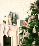 Il Natale ha decorato l'albero con il camino ed i calzini di Santa Immagini Stock