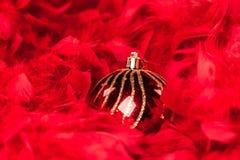 Il Natale ha decorato le palle - sopra le piume rosse Immagini Stock