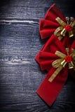 Il Natale ha legato i nodi rossi sulle feste del bordo di legno Fotografia Stock