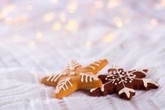 Il Natale ha lustrato il biscotto nella forma di stella e di fiocco di neve su luce a Immagine Stock