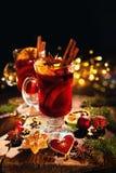 Il Natale ha sciupato il vino rosso con le spezie ed i frutti su Rus di legno fotografia stock libera da diritti