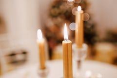 Il Natale ha servito la tavola con le candele gialle e l'albero di abete a fondo Immagine Stock