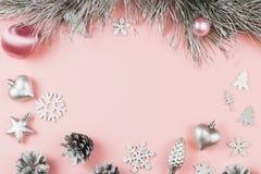 Il Natale incornicia con i rami dell'abete, i coni della conifera, le palle di natale e gli ornamenti d'argento sul fondo di rosa Fotografia Stock Libera da Diritti