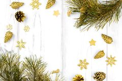 Il Natale incornicia con i rami di albero dell'abete, le pigne e gli ornamenti dorati su fondo di legno bianco, spazio della copi Fotografia Stock