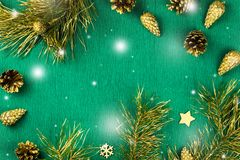 Il Natale incornicia con i rami di albero dell'abete, le pigne e gli ornamenti dorati su fondo verde caldo, caduta della neve Immagini Stock Libere da Diritti
