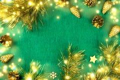 Il Natale incornicia con i rami di albero dell'abete, pigne, luci di natale, ornamenti dorati su fondo verde Immagini Stock