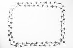 Il Natale incornicia con le decorazioni delle stelle dell'argento su fondo bianco Fotografia Stock