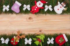 Il Natale incornicia fatto dei rami dell'abete decorati con gli archi bianchi pupazzo di neve e Santa Claus su un fondo di legno  Fotografia Stock Libera da Diritti