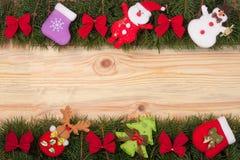 Il Natale incornicia fatto dei rami dell'abete decorati con gli archi rossi pupazzo di neve e Santa Claus su un fondo di legno le Immagine Stock