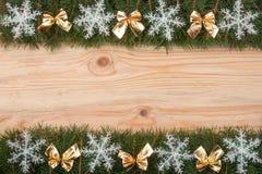 Il Natale incornicia fatto dei rami dell'abete decorati con i fiocchi di neve e l'oro si piega su un fondo di legno leggero Immagini Stock Libere da Diritti